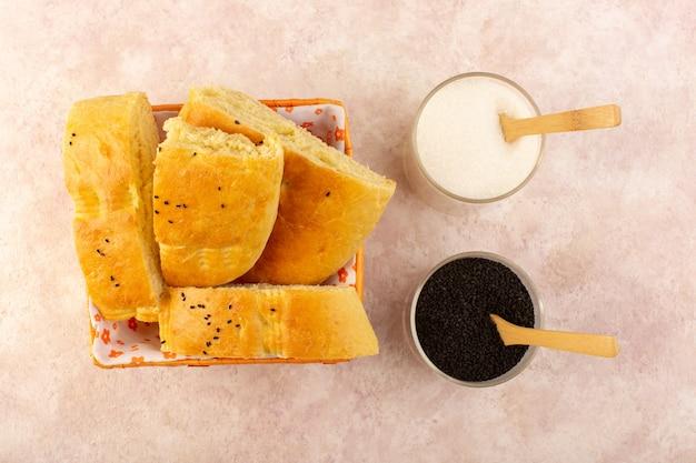 Une vue de dessus du pain cuit chaud savoureux frais tranché à l'intérieur du bac à pain avec du sel et du poivre sur rose