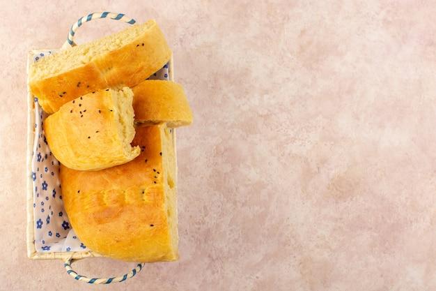 Une vue de dessus du pain cuit chaud savoureux frais tranché à l'intérieur du bac à pain sur rose