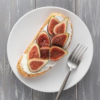 Vue de dessus du pain avec du fromage à la crème et des figues sur une assiette avec une fourchette