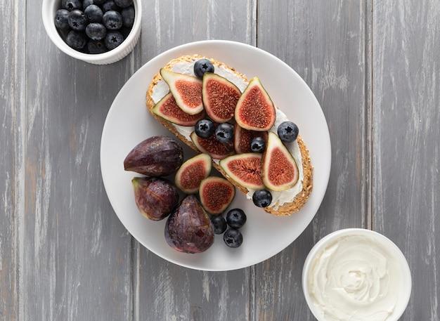 Vue de dessus du pain avec du fromage à la crème et des figues sur assiette