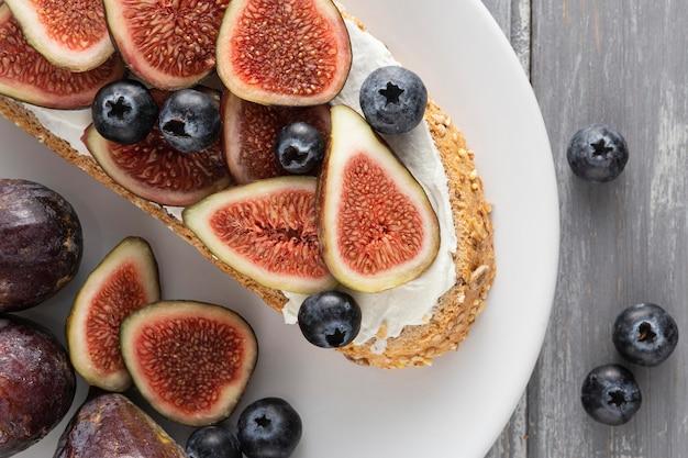 Vue de dessus du pain avec du fromage à la crème, des figues et des myrtilles