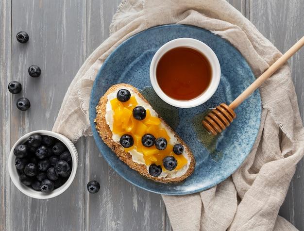 Vue de dessus du pain avec du fromage à la crème et des fruits sur une assiette avec du miel