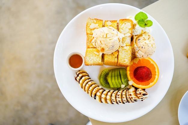 Vue de dessus du pain grillé au miel servi avec des fruits mélangés, des tranches de banane, de la crème glacée et garni de tranche d'amande et de sirop de miel dans une assiette blanche.