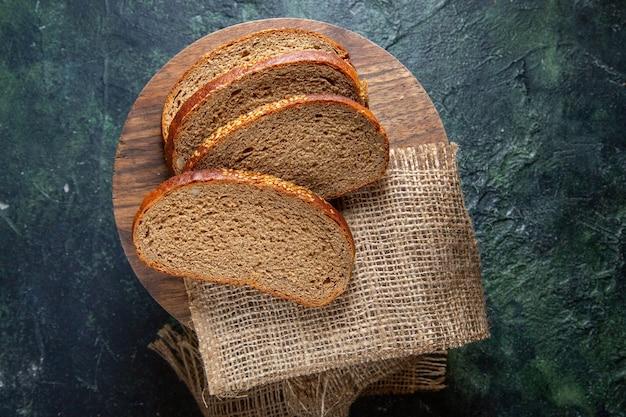 Vue de dessus du pain noir frais sur un bureau sombre