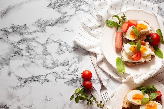 Vue de dessus du pain avec des œufs à la coque, des tomates et des hot-dogs