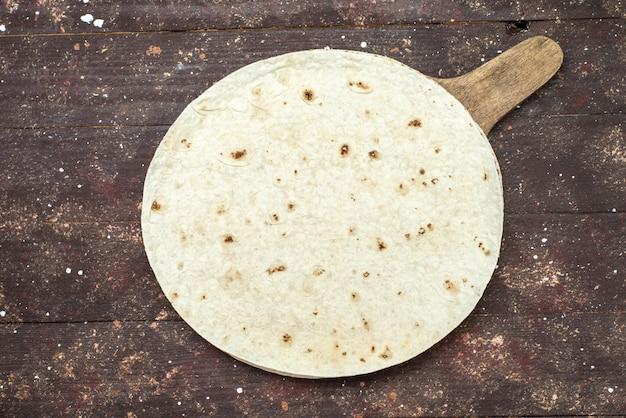 Vue de dessus du pain de pâte lavash rond comme sur le bureau en bois brun pâte à pâtisserie repas alimentaire