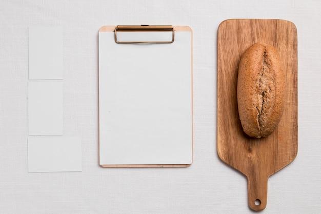 Vue de dessus du pain sur une planche à découper avec presse-papiers vierge