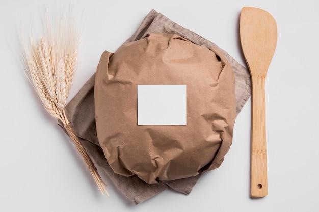 Vue de dessus du pain rond enveloppé avec une fourchette en bois