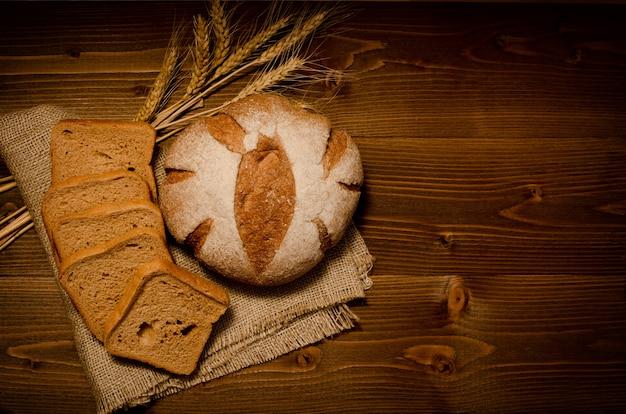 Vue de dessus du pain de seigle rond sur un sac, des morceaux de pain carrés, des épis de blé sur la table en bois