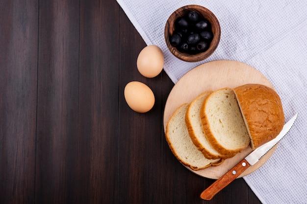Vue de dessus du pain tranché et du couteau sur une planche à découper avec des œufs et un bol d'olive noire sur un tissu et une surface en bois