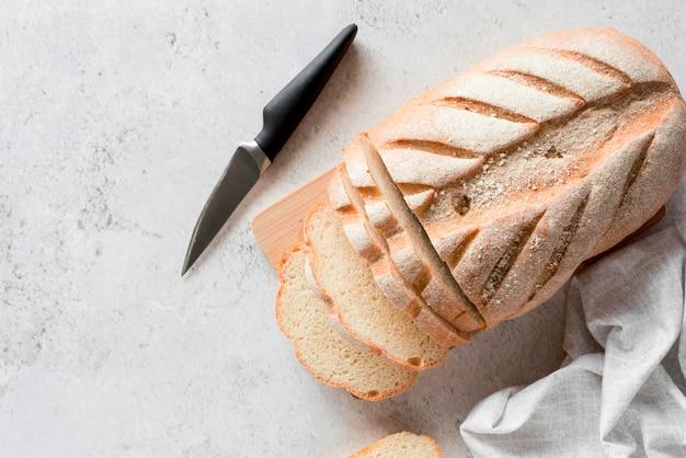 Vue de dessus du pain tranché sur une planche à découper avec un couteau
