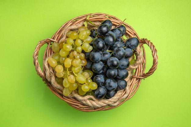Vue de dessus du panier en bois de raisins de raisins verts et noirs