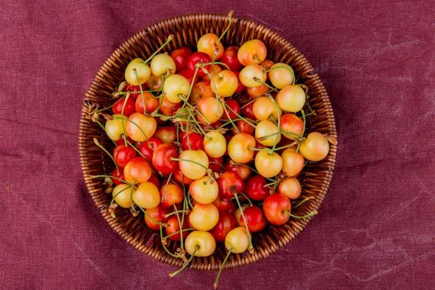 Vue de dessus du panier plein de cerises jaunes et rouges sur tissu bordo