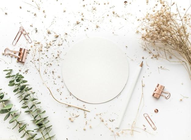 Vue de dessus du papier blanc sur la table de travail avec des accessoires de maquette et des fleurs sèches.
