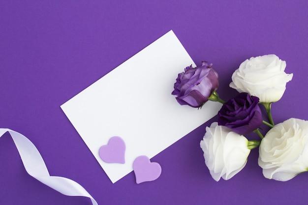 Vue de dessus du papier blanc vide pour le texte et les fleurs sur violet