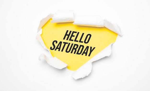 Vue de dessus du papier déchiré blanc et du texte bonjour samedi sur fond jaune.