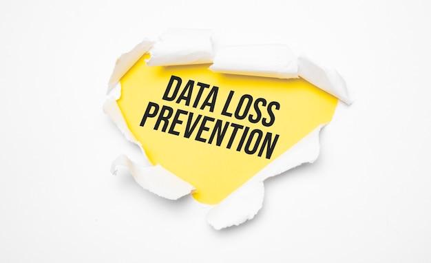 Vue de dessus du papier déchiré blanc et du texte prévention des pertes de données sur fond jaune.