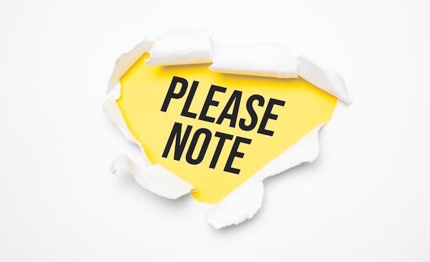 Vue de dessus du papier déchiré blanc et du texte veuillez noter sur fond jaune.