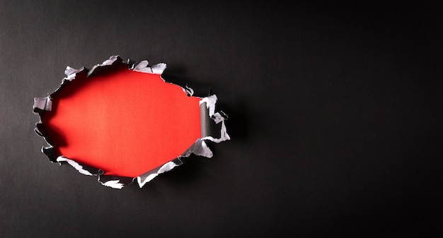 Vue de dessus du papier déchiré noir et du texte black friday sur le dos et le mur rouge. composition du vendredi noir.