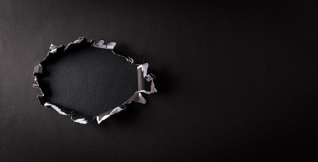 Vue de dessus du papier déchiré noir sur le mur du panneau arrière. composition du vendredi noir.