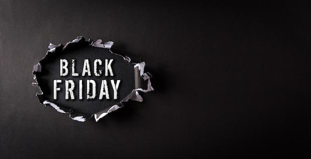 Vue de dessus du papier déchiré noir et le texte black friday sur le mur du panneau arrière