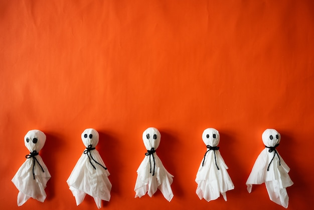Vue de dessus du papier fantôme sur fond de papier orange