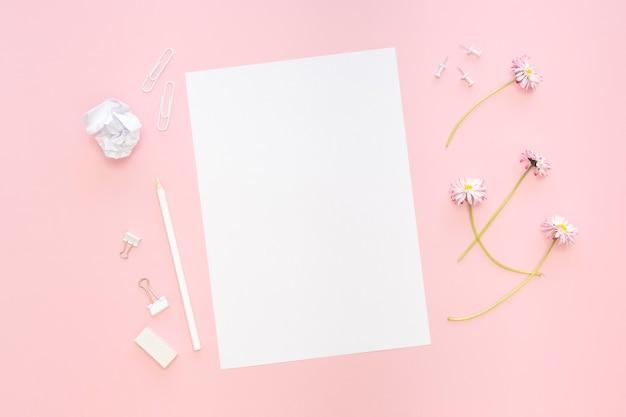 Vue de dessus du papier avec des fleurs et des crayons