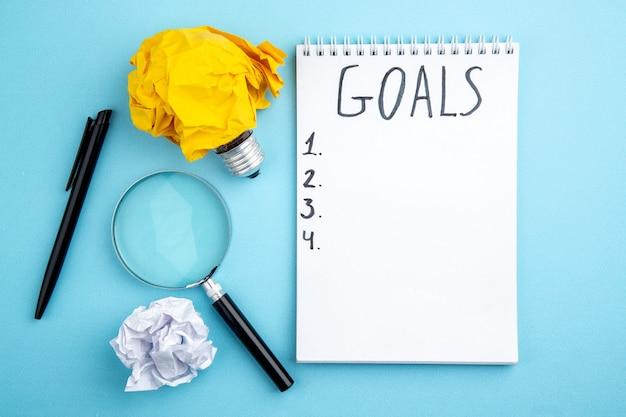 Vue de dessus du papier froissé avec idée ampoule concept stylo lupa objectifs écrits sur le bloc-notes sur fond bleu