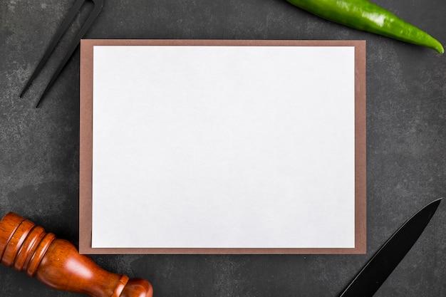 Vue de dessus du papier de menu vierge avec fourchette et poivre