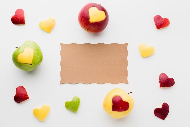 Vue de dessus du papier avec des pommes et des formes de coeur de fruits