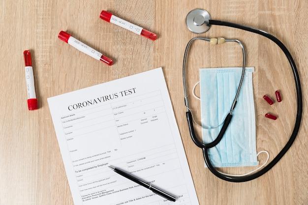 Vue de dessus du papier de test de coronavirus avec stéthoscope et pilules