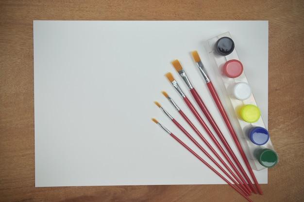 Vue de dessus du papier vide avec aquarelle de palette d'art et un pinceau sur fond de bois