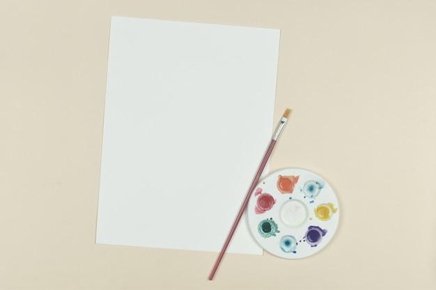 Vue de dessus du papier vide avec aquarelle de palette d'art et un pinceau sur fond orange