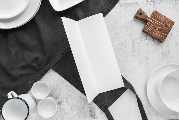Vue de dessus du papier vide avec des tasses et des assiettes