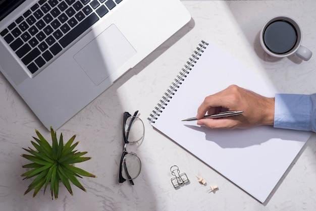 Vue de dessus du papier vierge en attente d'idée avec la main et le stylo