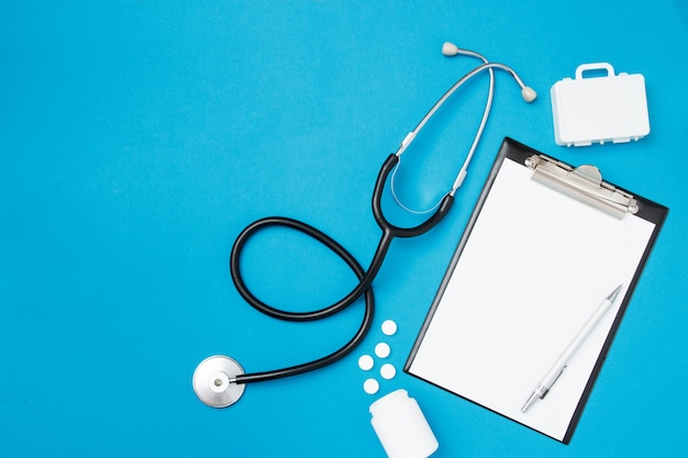 Vue de dessus du papier vierge pour écrire la prescription du médecin avec stéthoscope. pilules sur fond bleu. concept de soins de santé. vue de dessus, mise à plat, espace de copie.