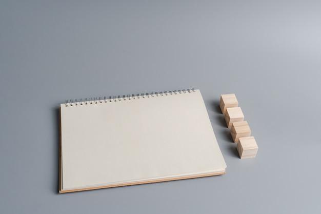 Vue de dessus du papier vierge pour ordinateur portable, bloc de cube en bois pour créer un signe, un symbole ou une lettre