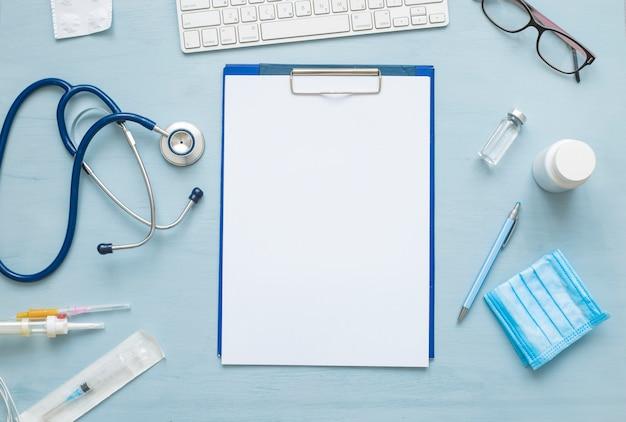 Vue de dessus du papier vierge pour la prescription de médecin. stéthoscope et attributs médicaux.