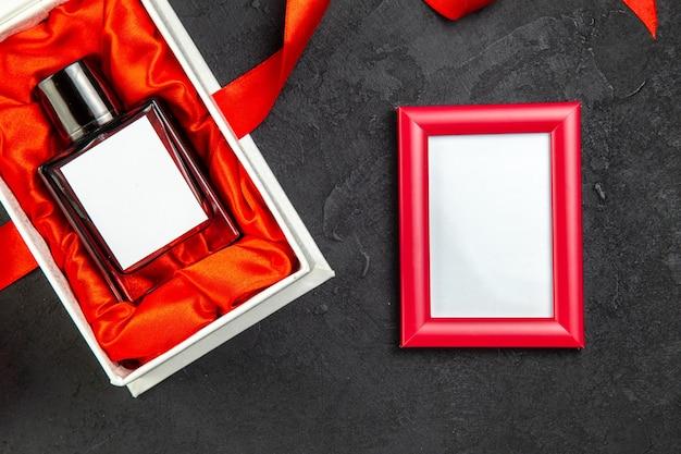Vue de dessus du parfum cher dans un emballage élégant en cadeau sur une table sombre