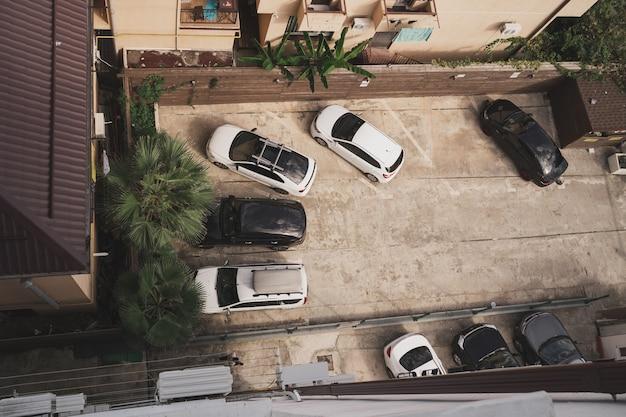 Vue de dessus du parking avec des voitures garant des voitures dans la cour des places de parking gratuites