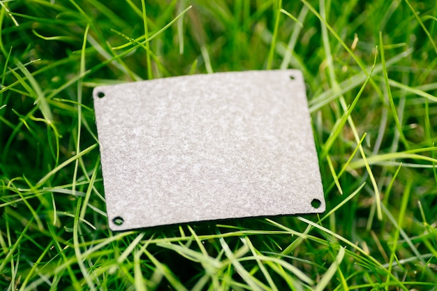 Vue de dessus du patch en cuir gris carré pour la disposition créative des vêtements d'herbe verte avec étiquette de logo.