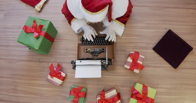 Vue de dessus du père noël écrivant sur une vieille machine à écrire. concept de lettres, écrivant une idée ou des noms. noël approche. préparation de la nuit de noël. promotion de ventes.