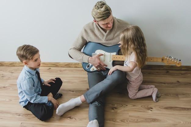 Vue de dessus du père avec sa guitare et ses enfants