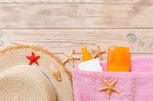 Vue de dessus du personnel de la plage d'été avec espace de copie. coquillages, bouteille de crème solaire, chapeau de paille et serviette sur fond de bois. concept de vacances d'été.
