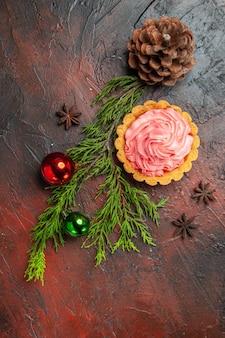 Vue de dessus du petit arbre de noël anis tarte jouets pomme de pin sur une surface rouge foncé