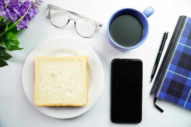 Vue de dessus du petit-déjeuner concept pain blanc sur assiette avec fleur de smartphone et une tasse de café