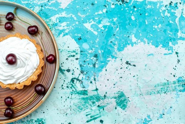 Vue de dessus du petit gâteau aux cerises aigres et crème sur bleu clair et blanc,