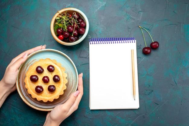 Vue de dessus du petit gâteau aux cerises que quelqu'un tient à côté de l'ordinateur portable