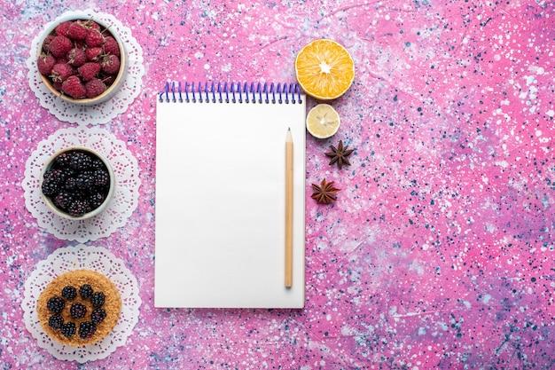 Vue de dessus du petit gâteau aux mûres avec des framboises fraîches et des mûres sur une surface rose clair