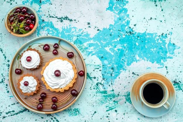 Vue de dessus du petit gâteau avec de la crème et des cerises sur le dessus à côté d'une tasse de café americano